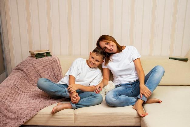 소파에 앉아 그녀의 웃는 아들과 포옹하는 어머니