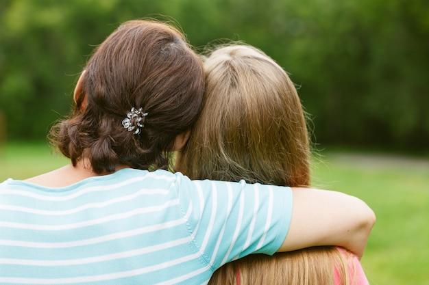 Мать обнимает дочь на природе в солнечный день