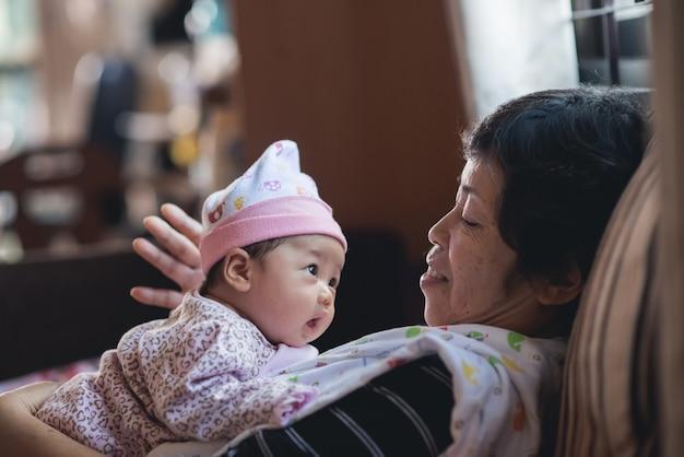 어머니 huging 그녀의 아기는 소파에 휴식