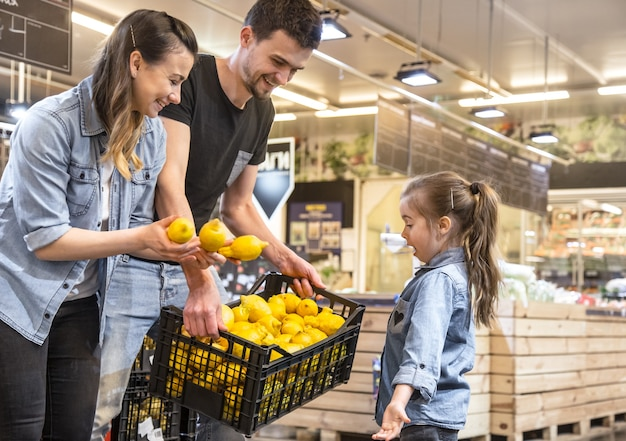 スーパーでレモンを選択する母、夫と娘