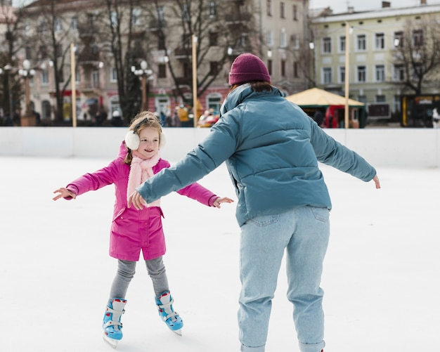 Mother ice skating with daughter