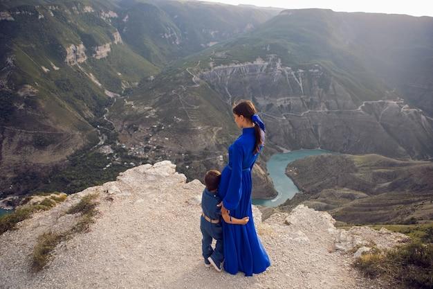 Мать в синем платье с сыном стоит на скале каньона сулак в дагестане.