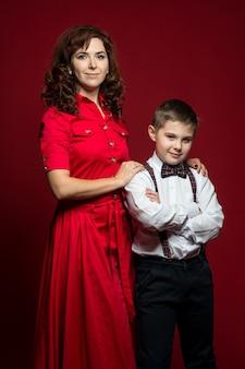 Мама в парадном платье нежно обнимает за плечи сына в белой рубашке.
