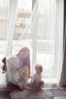 Мать в белом халате сидит с ребенком, белокурая дочь у большого окна дома