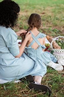青いドレスを着た母親が娘の髪を編む