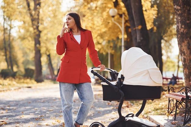 Мама в красном пальто гуляет с ребенком в детской коляске в парке осенью и курит.