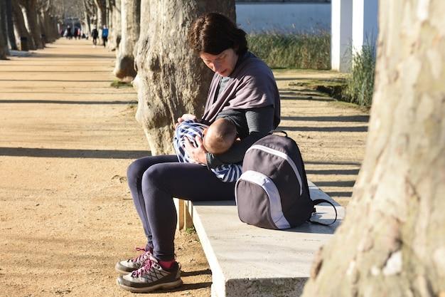 Мать в спортивной одежде кормит ребенка грудью