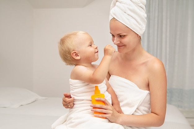 Mother and infant baby boy in white towels after bathing apply sunscreen or after sun lotion