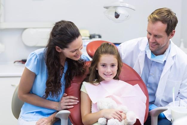 Мать взаимодействует с дочерью во время стоматологического осмотра