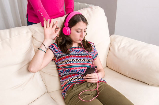 Mother is angry. teen girl with pink headphones is listening music with her phone at home.