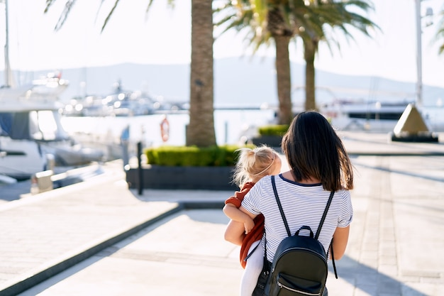 Mother is carrying her baby girl in her arms on a boat pier in porto montenegro.