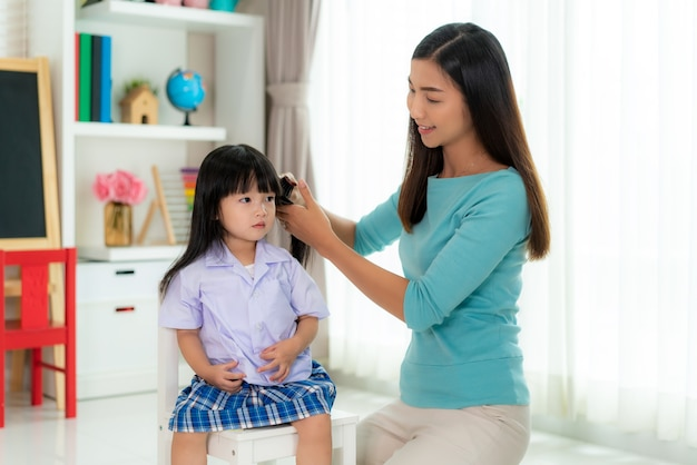 Mother is combing her daughter's hair on the morning before going to school