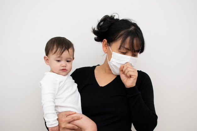 Mother is coughing in the mask while carrying her son