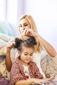 Mother is doing daughter's hair in bright full of sun light room