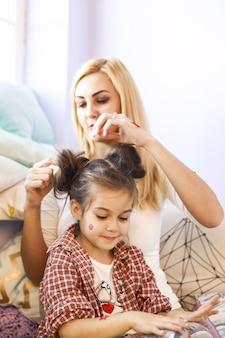 母は明るい日光の部屋で娘の髪をしています。
