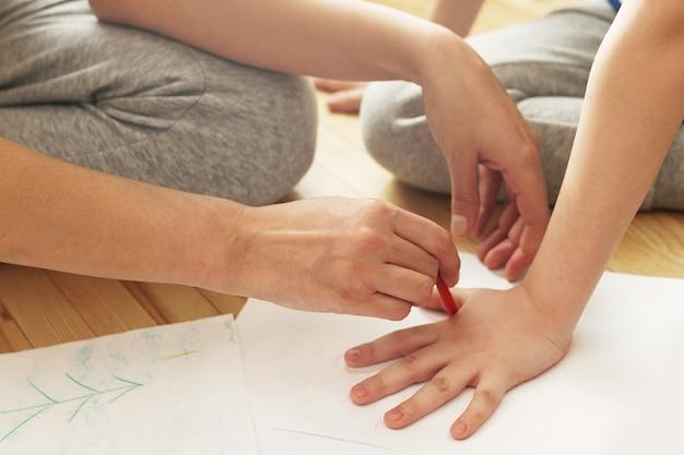 Мать рисует контур ладони сына на белой бумаге