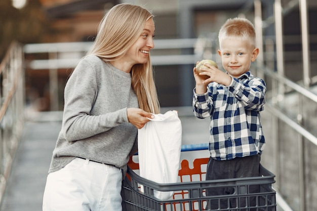 La mamma sta guidando in un carrello. famiglia in un parcheggio vicino a un supermercato.