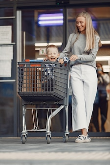 Mother is driving in a trolley. family in a parking near a supermarket.