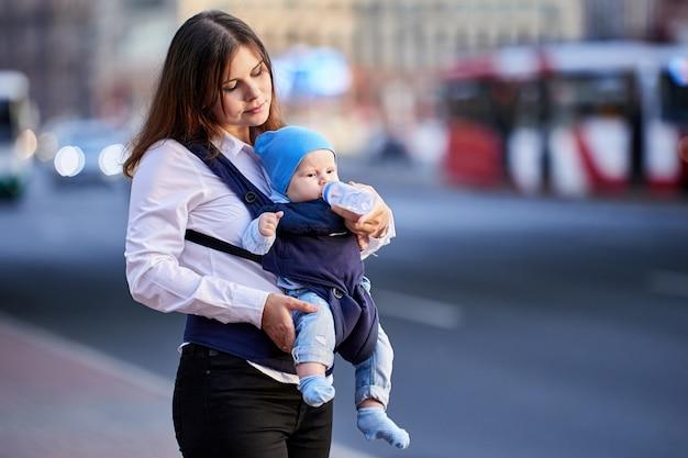 Мать кормит ребенка в слинге из бутылочки возле транспортной улицы