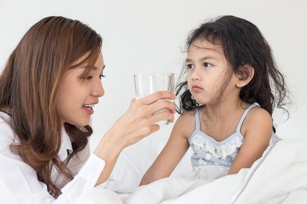 母は朝、娘に牛乳を与えています