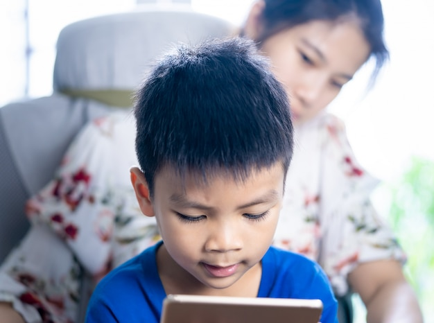 Mother is guiding her son to use tablet the right way