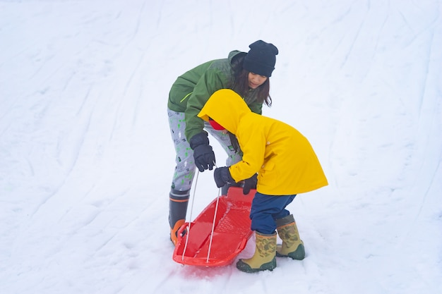 Mother is helping her daughter to ride the sled