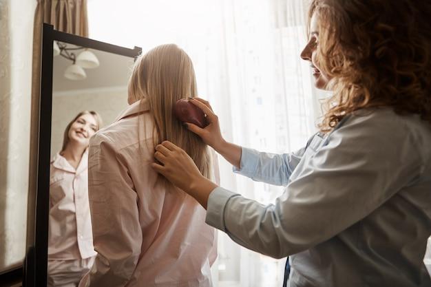 母は彼女の親しい友人です。ナイトウェアの鏡の近くに立って、自分を見て、笑顔で、髪をとかすお母さんを待って、リラックスして素敵な関係を持つことが幸せな若いヨーロッパの女の子