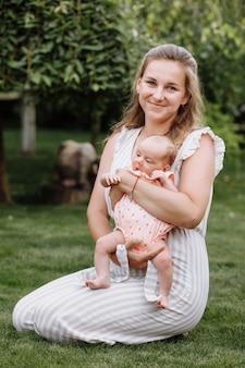 母は夏の日に彼女の女の赤ちゃんを屋外で抱きしめています
