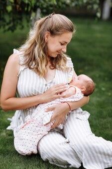母は夏の日に彼女の女の赤ちゃんを屋外で抱きしめています。