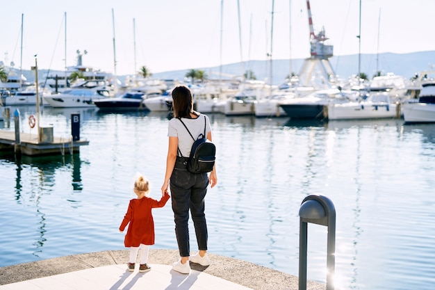 Mother is holding her daughter's hand and looking at boats in porto montenegro.