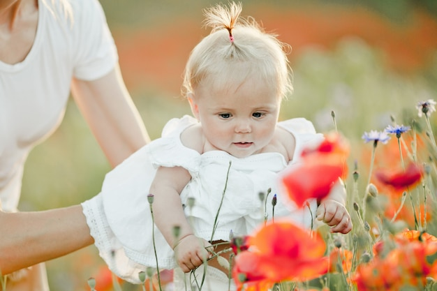 Mother is keeping her baby, a baby looks at flowers
