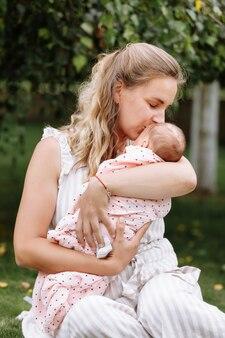 母親は夏の日に屋外で女の赤ちゃんにキスをしています。