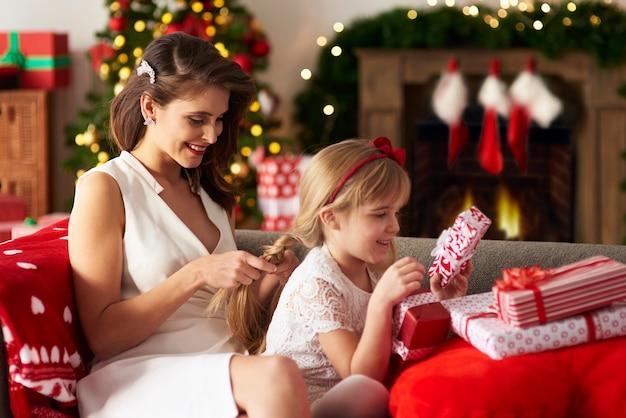 La madre sta intrecciando i capelli delle figlie