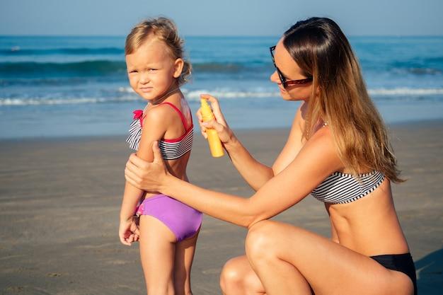 어머니는 해변에서 자외선 차단제를 등지고 있습니다.