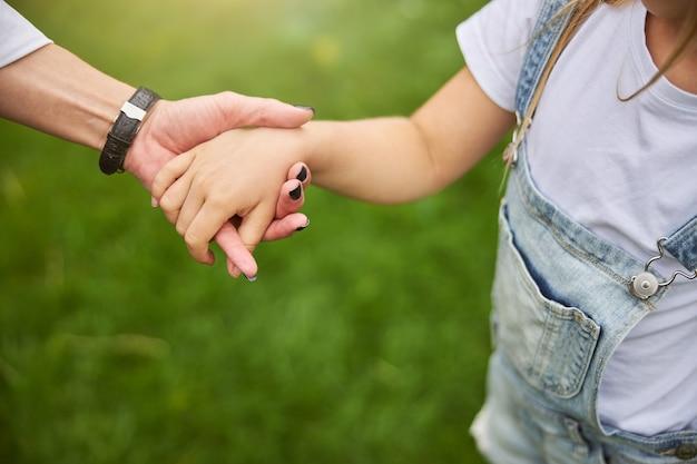어머니는 푸른 잔디에서 시간을 보내는 동안 어린 딸을 돌보고 관심을 기울이고 있습니다. 프리미엄 사진