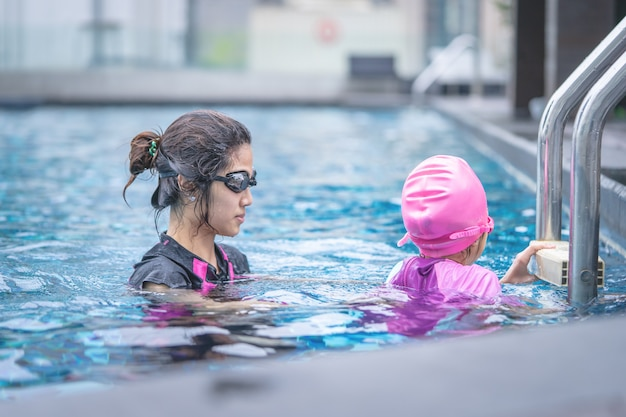 Mother is teaching her daughter to swim