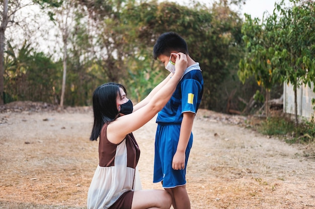 Mother is wearing a mask to protect her son from the covid-19 virus.