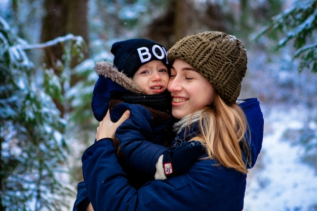 母は小さな子供を抱きしめている。雪に覆われたウィンターパークを散歩。