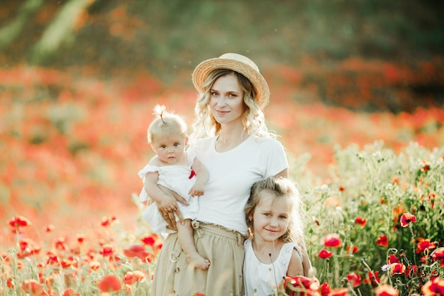 Mother keeps her baby and hugs  her elder daughter on the poppy field