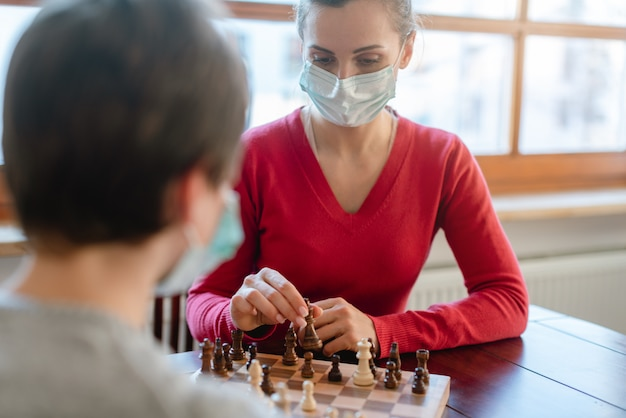 Mother and kid during coronavirus crisis playing chess at home