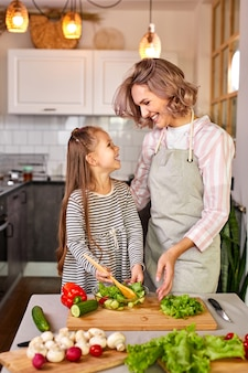 Mother and kid girl preparing healthy food for family, vegan salad made from fresh vegetables, mix together