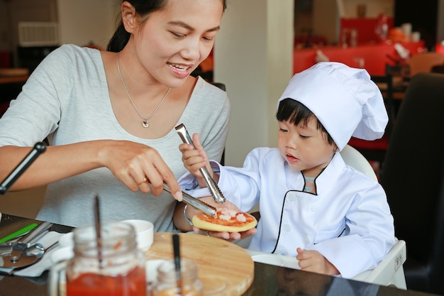 Mother and kid girl in a suit of the little chef make mini pizza, cooking child concept.