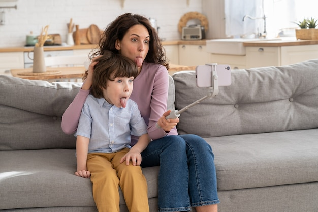 Mother and kid holding phone on selfie stick for video call showing tongue sitting on couch at home