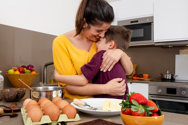 Mother and kid hugging in kitchen