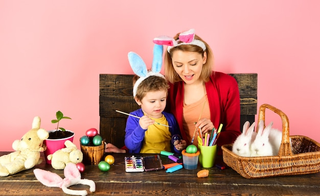 Mother and kid painting easter eggs