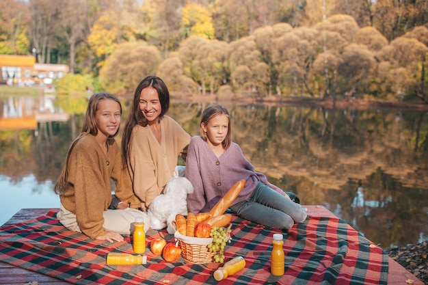 Mother and kids in autumn on picnic on the lake