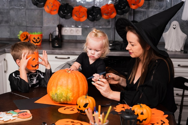 Mother and kids carving a pumpkin