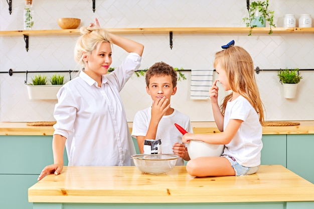 Mother and kids preparing pastry in kitchen
