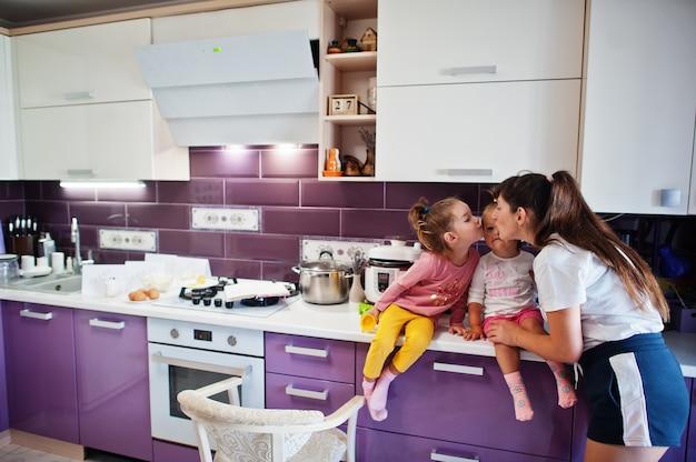 母は台所で彼女の女の子の子供たちにキスします、幸せな子供たちの瞬間。ママと2人の娘。