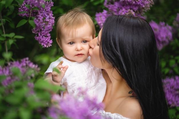 Мать целует дочь возле цветущей сирени. фиолетовый цвет. весеннее изображение